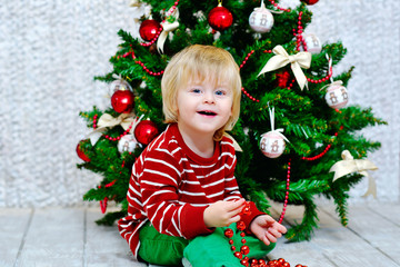 Positive blond toddler decorating Christmas tree with beads