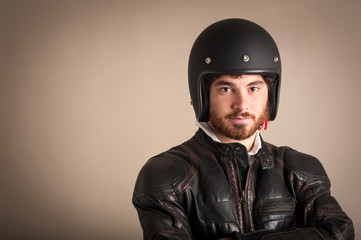 Portrait of confident young man with leather jacket and helmet