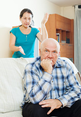 Upset mature man against wife at home