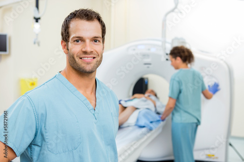 Nurse With Colleague Preparing Patient For CT Scan