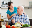 Smiling mature couple cooking food