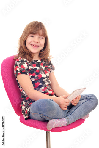 little girl sitting on chair and play with tablet pc