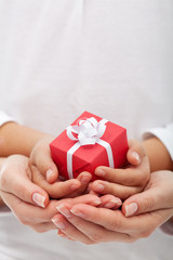 The joy of giving - small gift box in woman and child hands