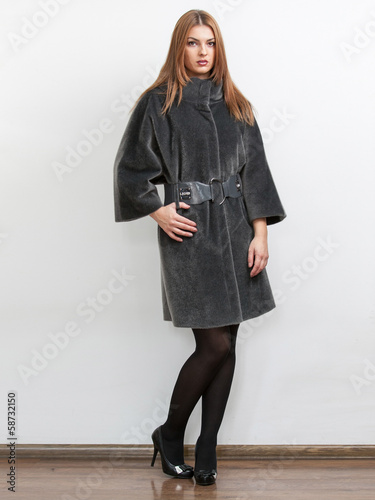 slim woman posing in gray fur coat against white background