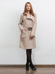 Sexy young woman wearing beige vintage coat with big collar