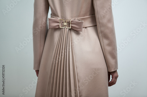 Photo of brown bow on back of women brown coat
