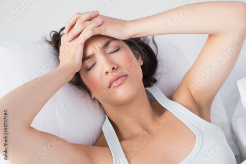 Sleepy woman suffering from headache in bed
