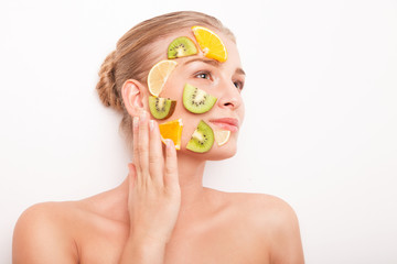 Smiling woman with fruit mask on her face isolated