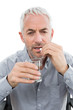 Close-up of a mature man with glass of water and pill