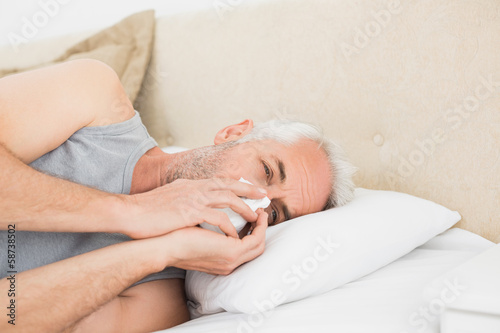 Close-up of a mature man suffering from cold in bed