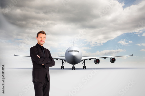Composite image of handsome businessman with crossed arms