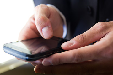 Hand's detail of Businessman  using a samrtphone