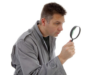 Man with raincoat is looking with magnifying glass over white ba