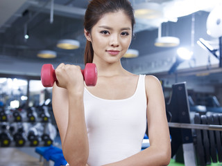 young woman holding a dumbbell in fitness center