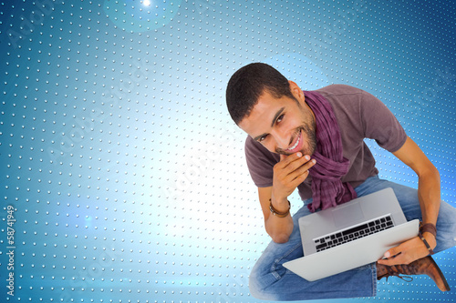 Composite image of thoughtful man sitting on floor using laptop