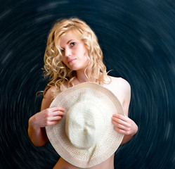 Young beautiful sexy woman with straw hat in hand