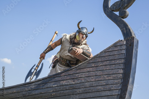 Strong Viking on his ship looking to beach