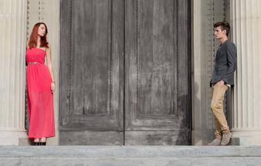 Elegant young couple separated by big wooden door