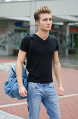 Attractive young man standing in city environment, with backsack