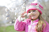 beautiful little girl near a flowering tree