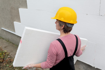 Female worker carry styrofoam sheet insulation, construction