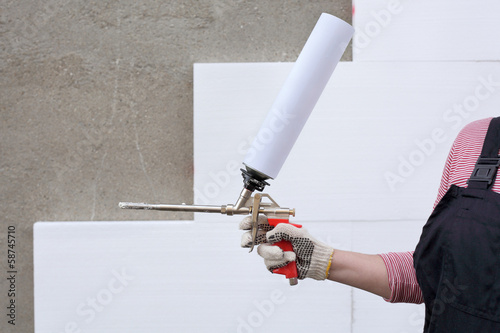 Worker hold polyurethane expanding foam glue gun applicator