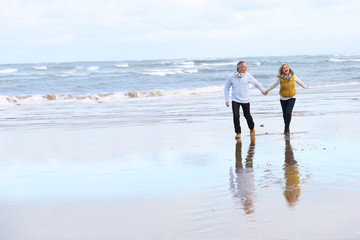 Senior couple running on the beach in winter time