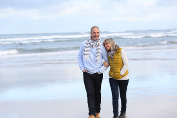 Senior couple walking on the beach in winter time