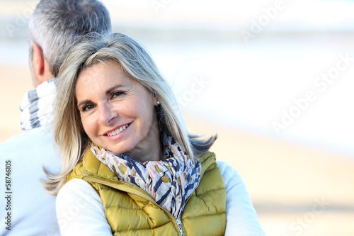 Senior woman relaxing with husband by the beach