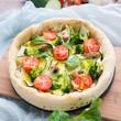 Pizza aus Vollkornteig mit frischem Gemüse belegt