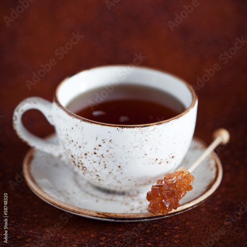 Cup of hot tea and rock candy sugar stick, selective focus