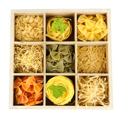 Nine types of pasta in wooden box sections close-up isolated