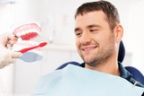 Dentist showing to man patient on mockup how to clean teeth poster