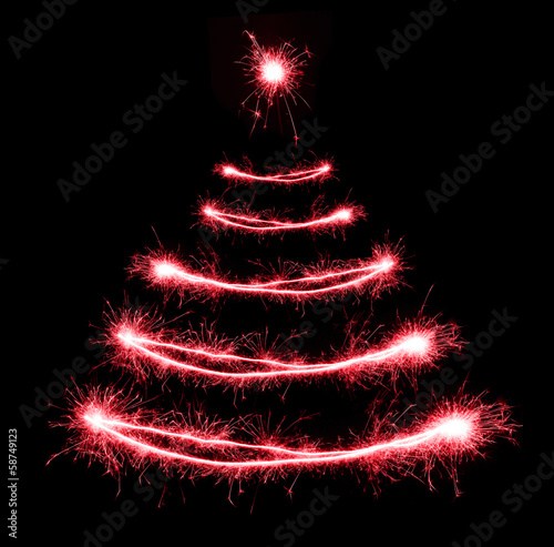 Christmas tree-shaped sparklers on black background