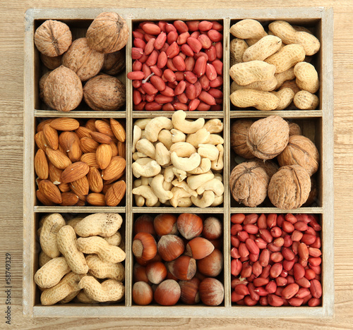 assortment of tasty nuts in  wooden box on table
