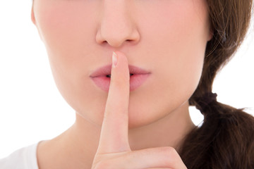 close up of young woman with finger on lips isolated on white