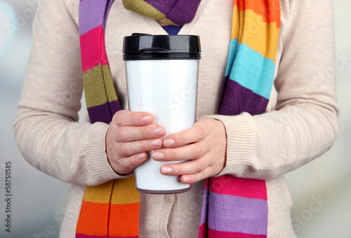 Hot drink in plastic glass in hands on bright background