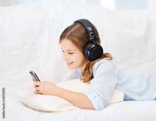 girl with smartphone and headphones at home