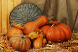 Pumpkins with wicker stand on straw on sackcloth background