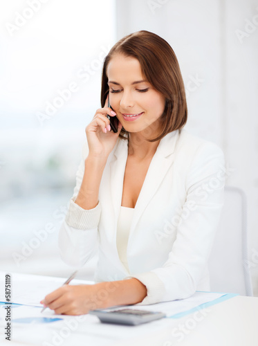 woman with papers, calculator and smartphone