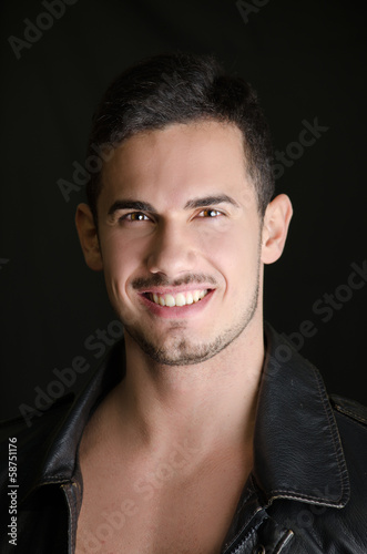 Portrait of attractive young man shirtless with leather jacket