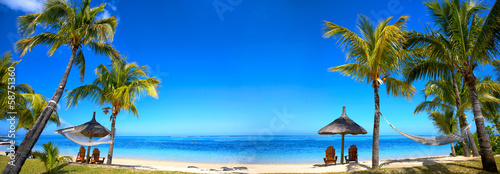 Poster Eiland Tropical beach panorama with chairs and umbrellas