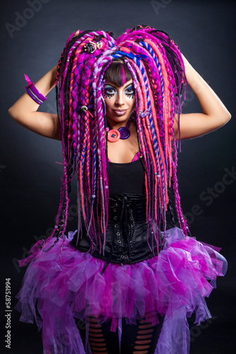 Portrait of a woman with multicolored dreadlocks and stylish mak