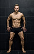 Sexy, muscular young man standing in underwear against dark wall
