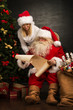 Portrait of happy Santa Claus sitting at his room at home with h