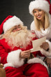 Portrait of happy Santa Claus sitting at home with his helper ne