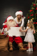Santa Claus holding white blank sign with family - mother and he