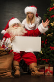 Santa Claus holding white blank sign with his wife and helper
