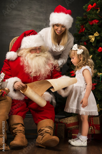 Santa Claus sitting at home with cute little girl and her mother