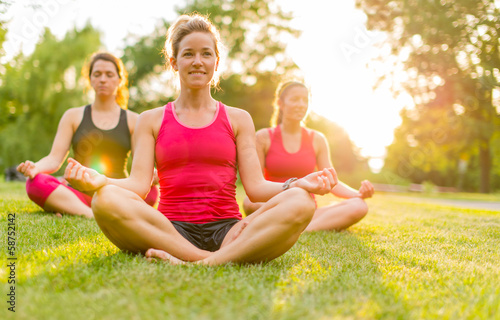 women doing yoga outdoors at sunset